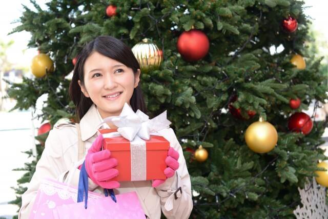 クリスマスツリーの前に立つ女性